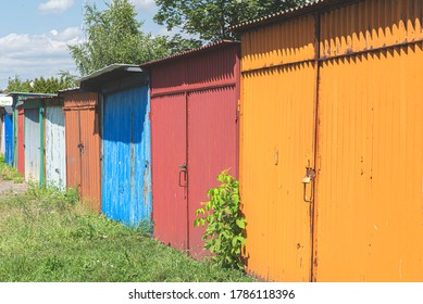 Row of colorful rusty garages or outdoor storage sheds. Old garage door closed with latch, padlock or hasp