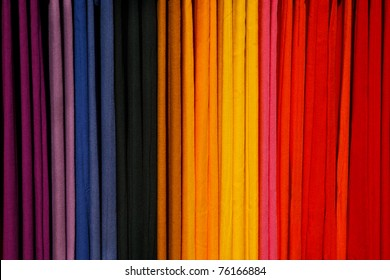 A row of colorful scarves hanging on a rack