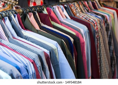 row of colorful row shirts hanging on