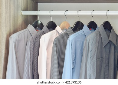 row of colorful shirts hanging in wardrobe