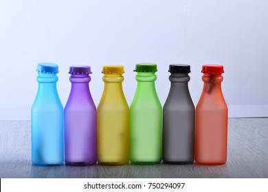 Row of colorful soft drinks on grey background background. Energy drinks containers with various flavors on wooden table. Colour choice and containers concept. Set of bottles in different color.