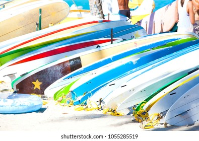 Row of colorful surfboards lined up on sandy beach in Hawaii