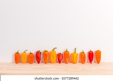 Row of colorful sweet peppers on wooden surface. Fresh vegetables.