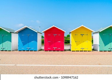 A row of colorful wooden beach huts on the beach