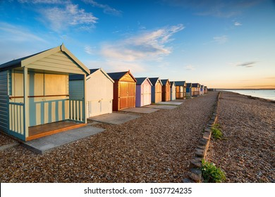 A row of colourful beach huts on the Solent at Calshot on the edge of the New Forest near Southampton in Hampshire