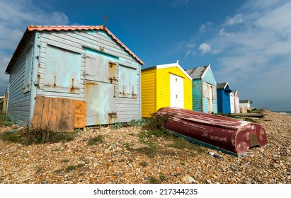 A row of colourful beach huts on a shingle beach at St Leonards On Sea in Hastings, East Sussex