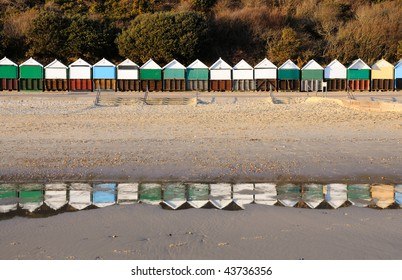 A row of colourful beach huts reflected in pools of seawater left by the falling tide.