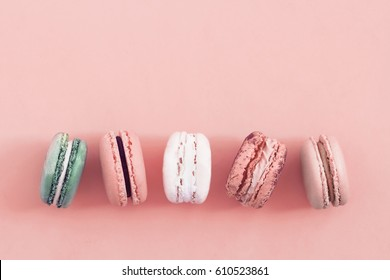 Row of colourful french macaroons on pale pink background. Top view, copy space for text. Social media, blogging concept