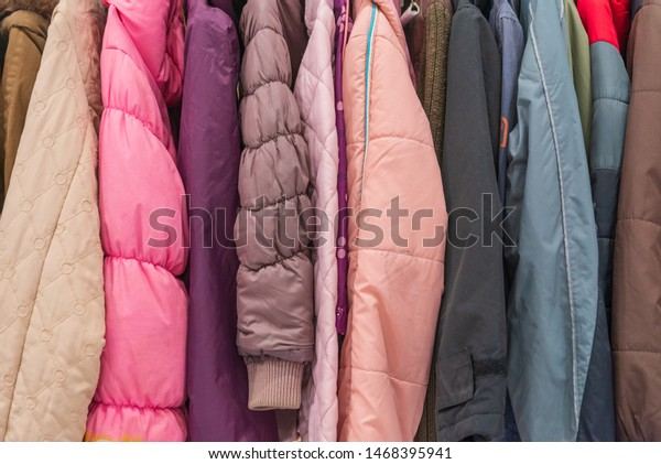 Row of colourful tone of adult winter jackets hang on aluminium hanger clothes rack in retail fashion store or second hand outlet shop.
