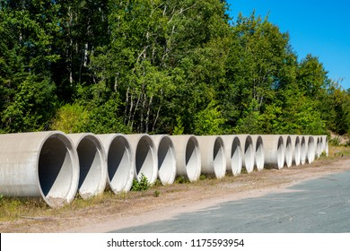 A row of concrete pipes beside a road. This is the type of pipe used for sewers. Trees and blue sky in the background.