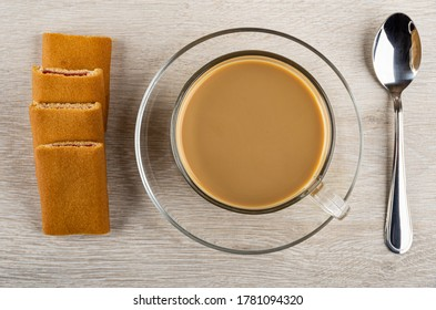 Row of cookies with filling, cup of coffee with milk on saucer, teaspoon on wooden table. Top view