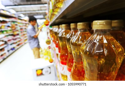 Row of cooking oil bottles on shelf for sale and blurred consumer shopping in supermarket in shopping mall. Selective focus and close-up to the cooking oil bottles row.