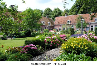 Row of cottages in a big flower garden in Edam, the Netherlands