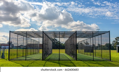 A row of cricket practice nets on green grass and with a blue sky in Melbourne, Victoria, Australia