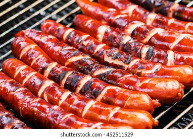row of crispy sausages lying on a grill