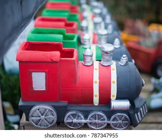Row of cute model trains in red and green representing privatisation of the railway with Virgin and Carillion