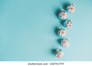 A row of decorative Christmas tree decorations on turquoise background.