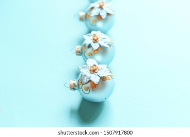 A row of decorative Christmas tree decorations on menthol background.