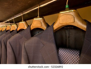 A row of designer suits hanging in a menswear store.