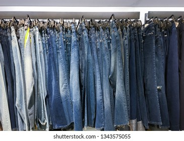 Row of different blue Jeans on hanging –white background