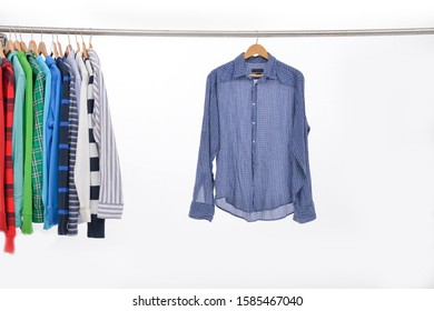 Row of different checked long sleeve and striped shirt ,hoodie and with blue shirts on hanger