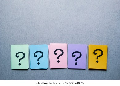 Row of different colored cards with question marks on a textured grey background with copy space above and below in a conceptual image