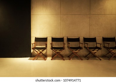 Row of director's chair on gray cement background in studio.