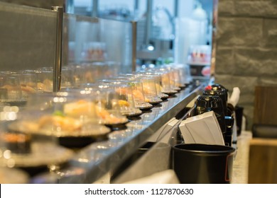 Row of dishes in belt japanese food buffet. trendy popular restaurants. healthy food type of boiled instead fried trans-fat. image for background, objects and copy space.