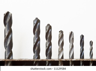 Row of drill bits in a stand, against a white background.