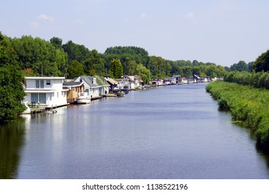 A row of Dutch houseboats in the Lange Wetering, city of Almere.
