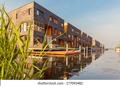 Row of Dutch modern canal houses in Almere reflected in the water