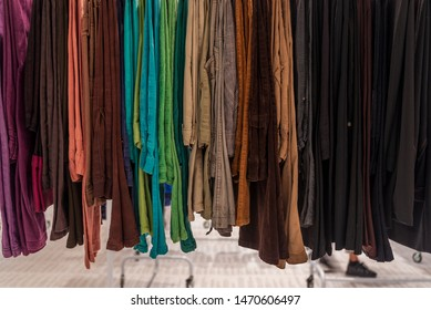 Row of earth tone colour fabric jeans or denim trousers and slacks hang on hanger. Various trousers in retail fashion store. Second hand retro style of dark tone slacks sold in outlet shop.