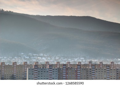 Row of Eastern European Socialist era tower blocks with snowy single-family houses and towering forested Bukk Range of North Hungarian Mountains, Diosgyor Miskolc Borsod county Hungary Central Europe