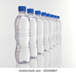 row of eight water bottles disappearing into distance with focus on front bottles
