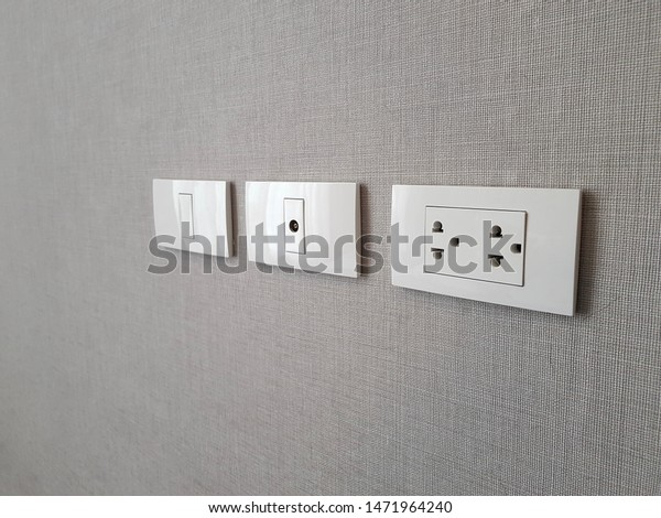 Row of electric outlet set in bedroom wall, TV outlet , cable outlet and Electronic plug with Asia style on grey fabric texture wallpaper, cable television. Electricity concept.