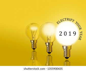 A row of electrified incandescent light-bulb with the message: Electrify your year 2019.