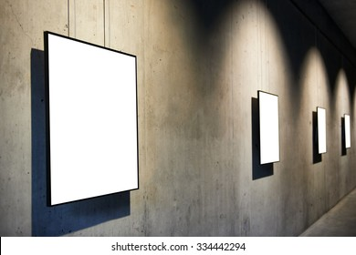 Row of empty black frames on concrete wall in the gallery isolated on white