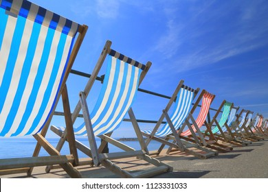 Row of empty deck chairs on the beach in Devon