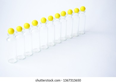 Row empty glass medical tubes and yellow vitamins ball placed at the top on a light gray background. Group Medicine glass jar, capacity for liquid medicines with open neck without stopper.