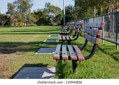 Row of empty park bench seats at sports field
