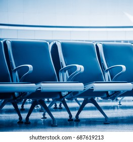 row of empty seats in airport lobby,blue toned,china.