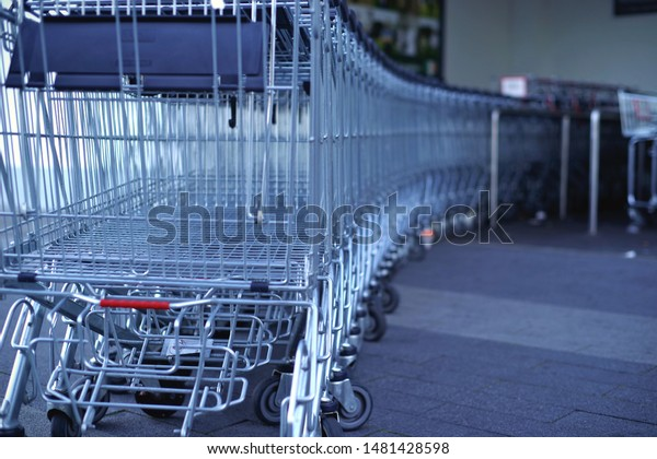 Row of empty shopping carts outside of supermarket entrance with blur background