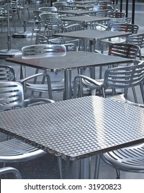 Row of empty tables and chairs outside a restaurant