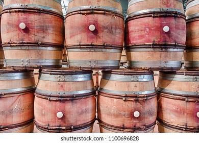 A row of empty wine barrels are stacked up in a winery to make an interesting background.