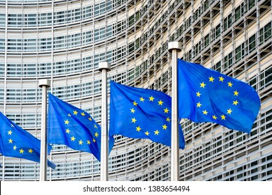 A row of european flags blowing in the wind at full-mast in front of the Berlaymont building, headquarters of the European Commission, the executive of the European Union (EU) in Brussels, Belgium.
