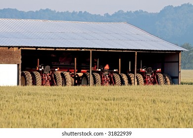 Row of farming tractors parked side by side in a shed.  Viewed across a field of young wheat crops.  An early morning haze clouds the trees and sky in the distance.