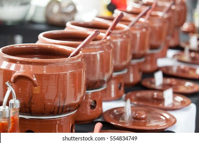 Row of feijoada cookware aligned on table