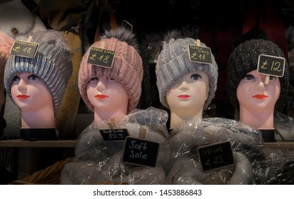 A row of female mannequin heads on a market stall wearing a knitted hat