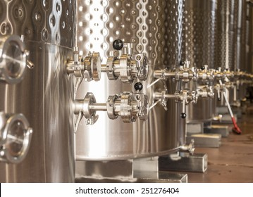 A row of fermentation tanks in a winery showing the valves and knobs used to control the flow of wine.