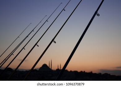 A row of fishing rods and distant mosque silhouetted at sunset from Galata bridge in Istanbul, Turkey.